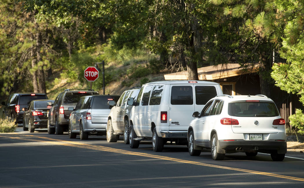 Vehicles leave Yosemite National Park, Calif., on Tuesday, July 24, 2018, as the Ferguson Fire burns nearby. Parts of the park, including Yosemite Valley, will close Wednesday as firefighters work ...