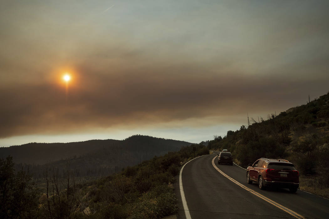 As smoke from the Ferguson Fire fills the sky, vehicles leave Yosemite Valley in Yosemite National Park, Calif., on Tuesday, July 24, 2018. Parts of the park, including Yosemite Valley, will close ...