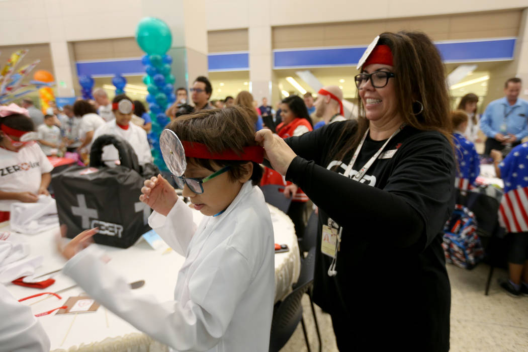 Mathew Maldonado, 11, gets dressed in team Docs & Jocks gear with the help of Sharon Chayra of Code 3 Emergency Partners during the Sixth Annual Paper Plane Palooza in Terminal 3 at McCarran I ...