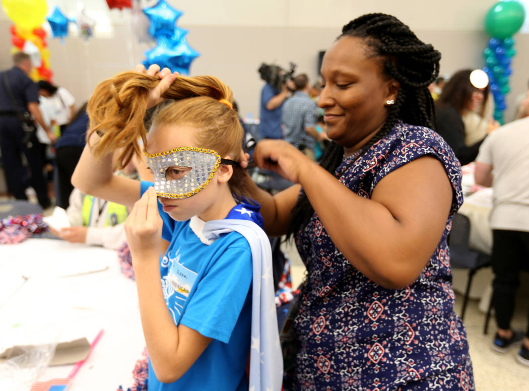 Kiana Harworth, 11, gets dressed in team American gear with the help of Ashley Nelson during the Sixth Annual Paper Plane Palooza in Terminal 3 at McCarran International Airport in Las Vegas Wedne ...