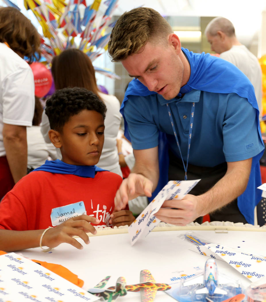 Jamal Adams, 10, gets help with folding from Andrew Porrello during the Sixth Annual Paper Plane Palooza in Terminal 3 at McCarran International Airport in Las Vegas Wednesday, July 25, 2018. More ...