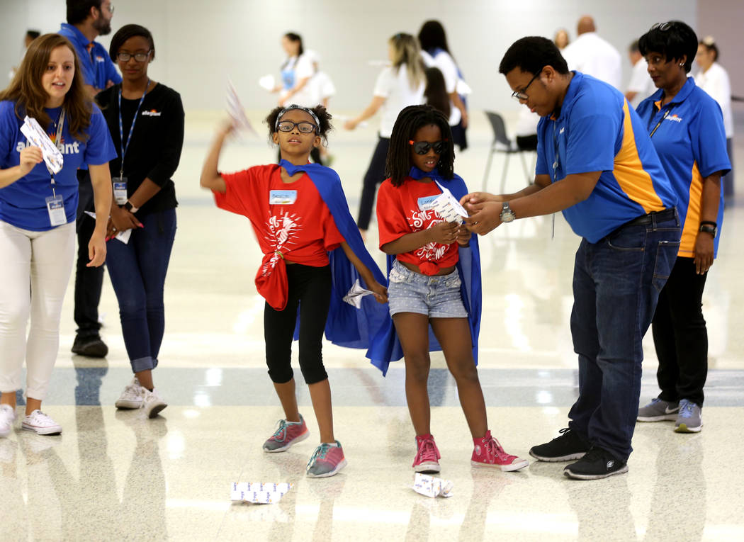 Brooklyn Lee, 9, left, and London Trowers, 8, test their planes with the help of Krysta Levy, left, and Taurean Hill of Allegiant Airlines during the Sixth Annual Paper Plane Palooza in Terminal 3 ...