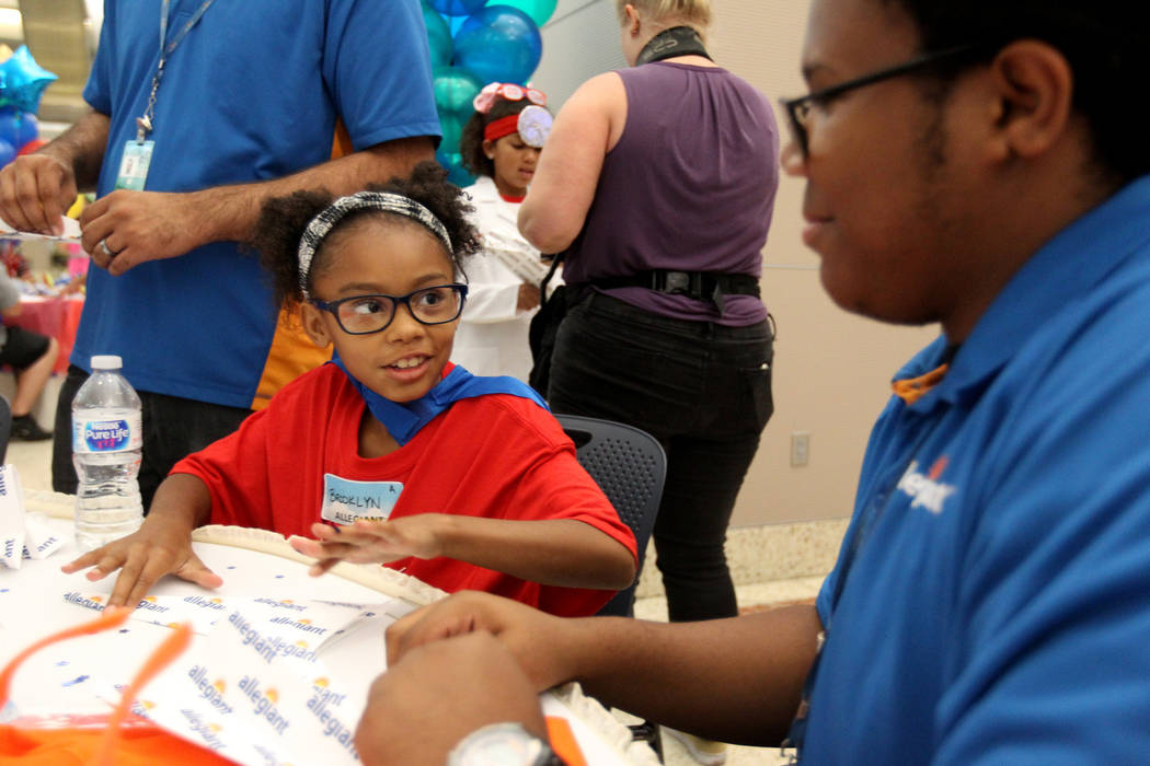 Brooklyn Lee, 9, and Taurean Hill of Allegiant Airlines fold planes during the Sixth Annual Paper Plane Palooza in Terminal 3 at McCarran International Airport in Las Vegas Wednesday, July 25, 201 ...