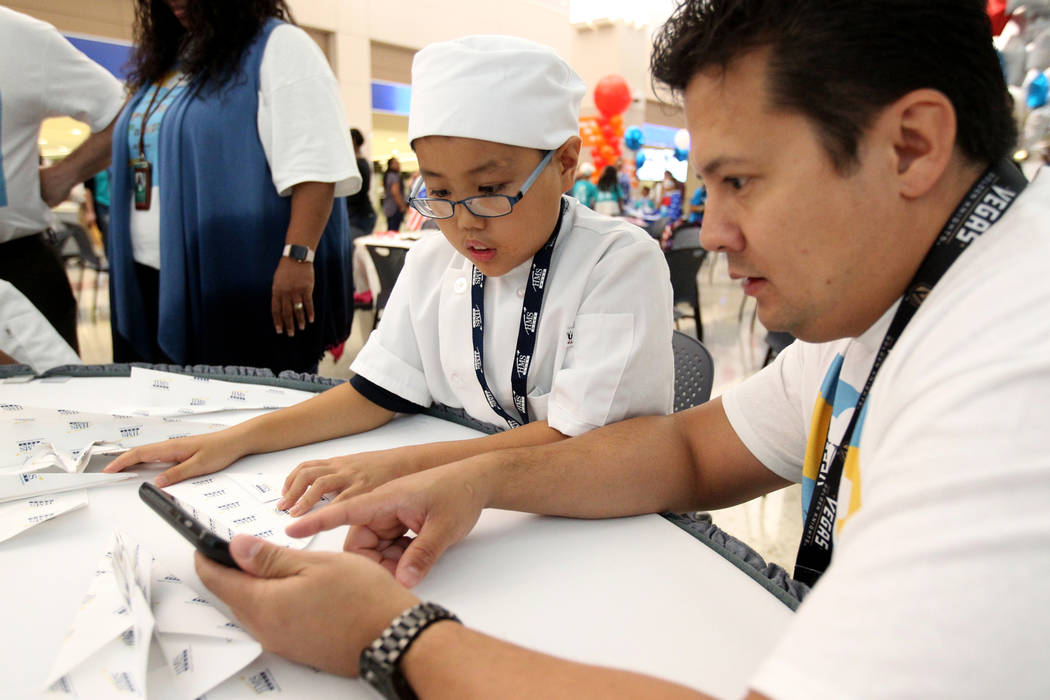 Hiromitsu Kosaka, left, and Chris Mattux fold planes during the Sixth Annual Paper Plane Palooza in Terminal 3 at McCarran International Airport in Las Vegas Wednesday, July 25, 2018. More than 70 ...