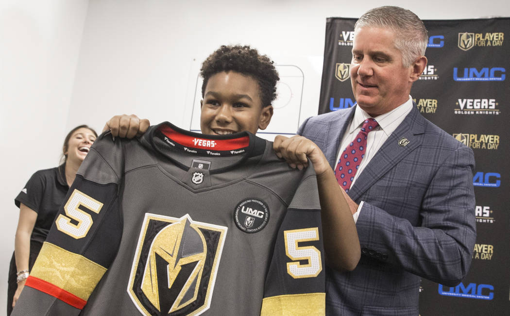 Kai Aiden Fields, middle, shows off his new jersey with Golden Knights President Kerry Bubolz during UMC's Player for a Day event where pediatric patients get to experience a day in the life of a ...