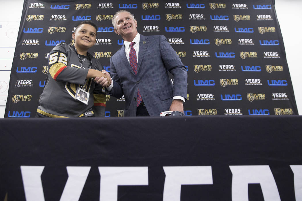 Jacob Grimblot, left, shakes hands with Golden Knights President Kerry Bubolz after signing his contract during UMC's Player for a Day event where pediatric patients get to experience a day in the ...