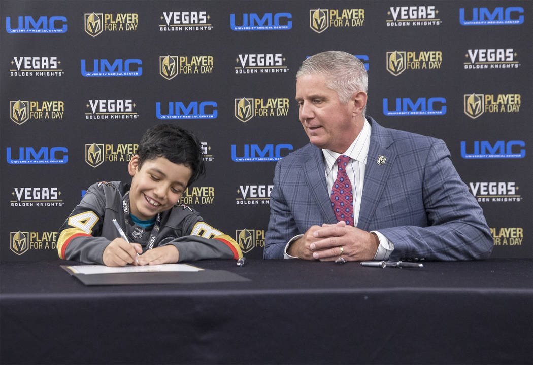 Denali Quintana, left, signs his contract with Golden Knights President Kerry Bubolz during UMC's Player for a Day event where pediatric patients get to experience a day in the life of a Vegas Gol ...