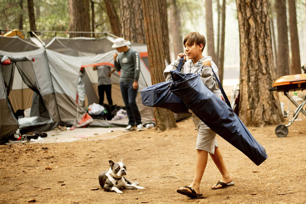 River Martinez, 10, breaks camp at the Upper Pines Campground in Yosemite National Park, Calif., on Wednesday, July 25, 2018. Martinez's family, visiting from Los Angeles, had to cut their stay sh ...