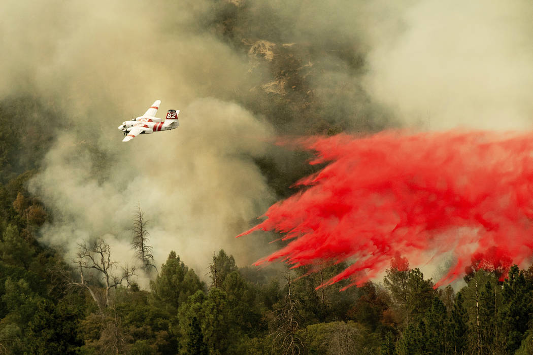 An air tanker drops retardant while fighting to stop the Ferguson Fire from reaching homes in the Darrah community of unincorporated Mariposa Count, Calif., Wednesday, July 25, 2018. (Noah Berger/AP)