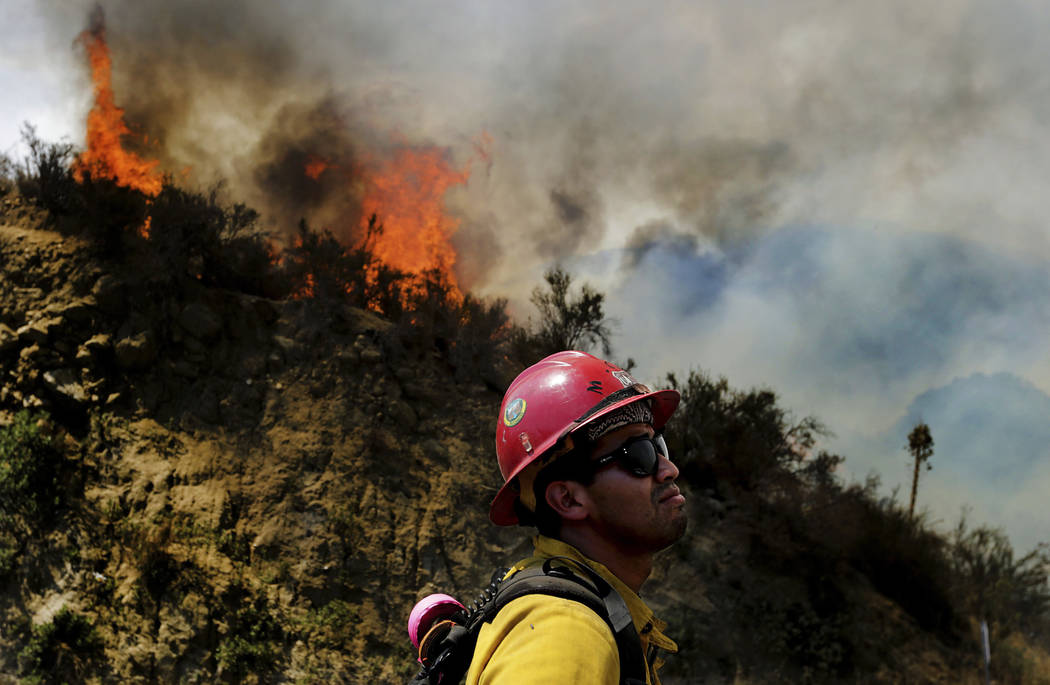 A firefighter watches as the Cranston fire grows to more 1,200 acres in the San Bernardino National Forest above Hemet, Calif., Wednesday, July 25, 2018. (Terry Pierson /The Orange County Register ...