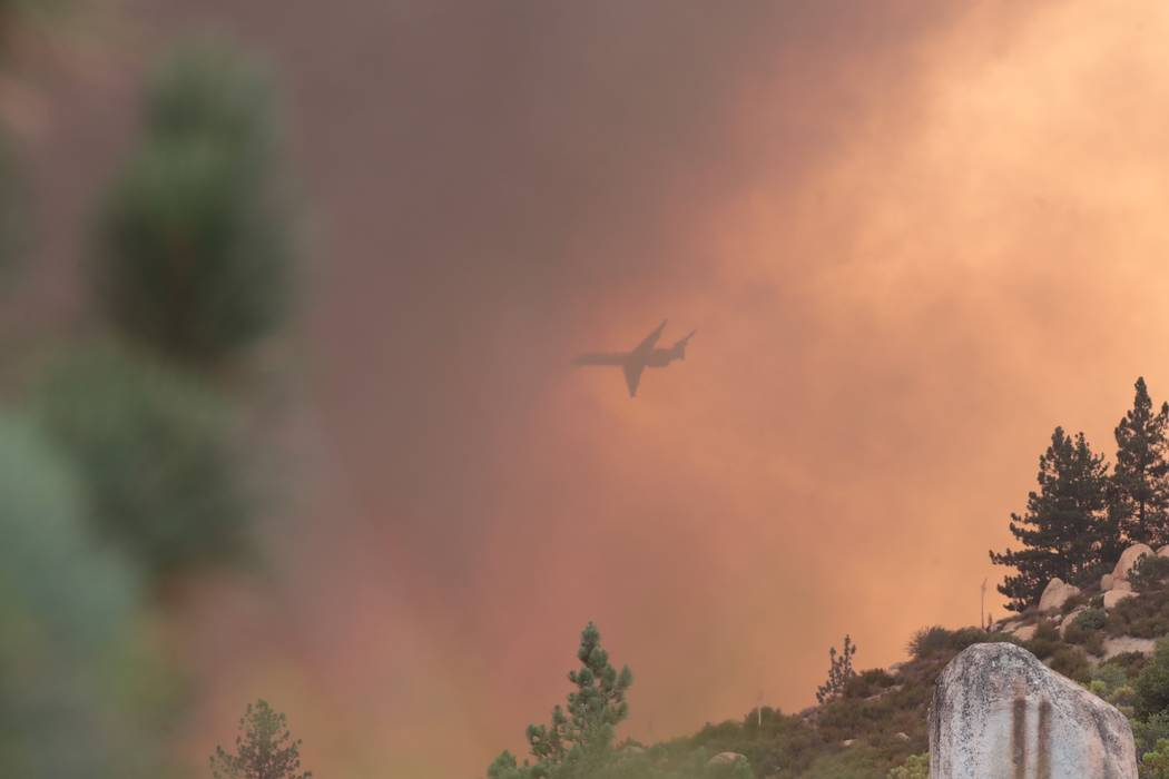 A passing airplane can be seen through the smoke from the Cranston Fire near Idyllwild, Calif. in the San Jacinto Mountains, nearly 50 miles northwest of Palm Springs, Calif., Wednesday, July 25, ...