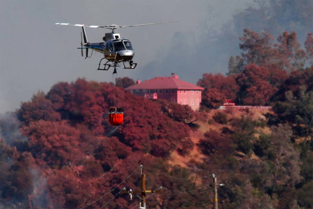 A helicopter battling a fire on Mt. Diablo passes a home covered in fire retardant, Wednesday, July 25, 2018, above Marsh Creek Road east of Clayton, Calif. (Karl Mondon/San Jose Mercury News via AP)