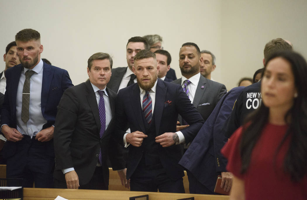 Conor McGregor, center, appears in court with co defendant Cian Cowley, left, during a hearing, Thursday, July 26, 2018, in the Brooklyn borough of New York. The mixed martial arts star pleaded gu ...