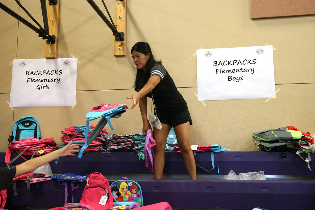 Volunteer Stephanie Mitchell helps fosters children find a backpack during an event sponsored by Foster Change at the Clark County Family Services Department in Las Vegas, Thursday, July 26, 2018. ...