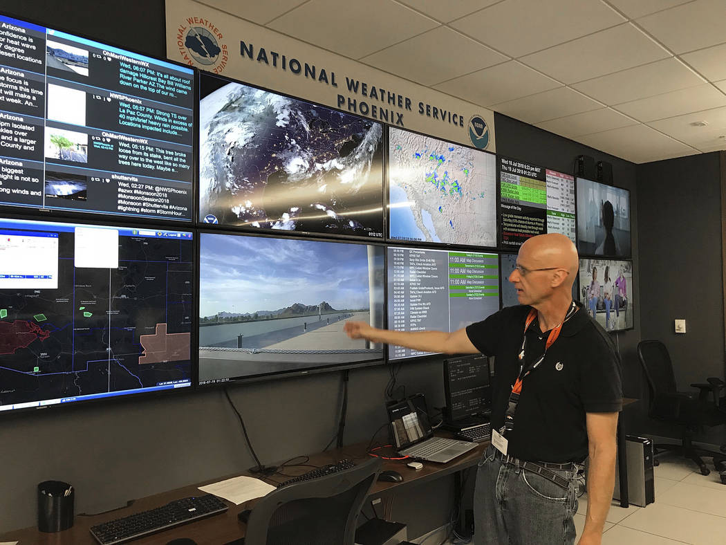 In this Wednesday, July 18, 2018 photo, National Weather Service forecaster Marvin Percha reviews monitors that track satellite and Doppler radar images, as well as his colleagues' forecasts poste ...