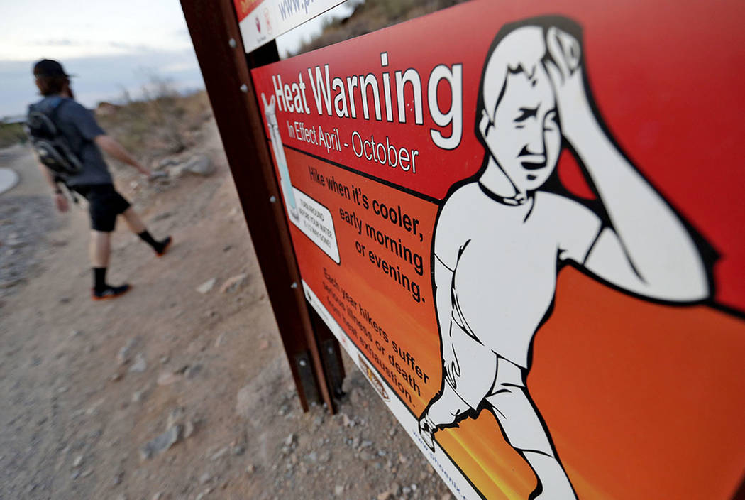 In this Tuesday, July 24, 2018 photo, a hiker walks past a heat warning sign at sunrise, in Phoenix. (AP Photo/Matt York)