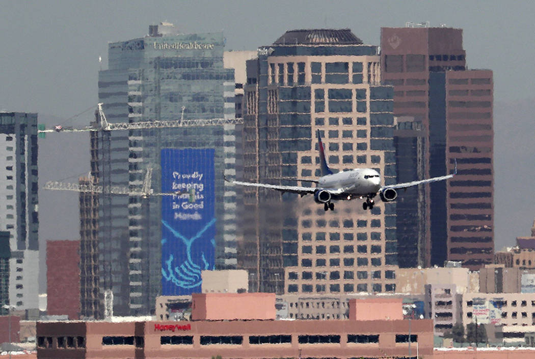 In this Monday, July 23, 2018 photo, heat ripples blur the downtown skyline as a jet lands in Phoenix, Ariz., as temperatures exceed 100 degrees in the morning hours. (AP Photo/Matt York)