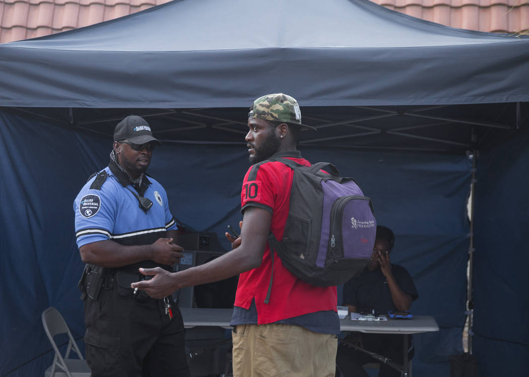 Allied Universal Security officer Shaun Smith, left, checks people into the city of Las Vegas' homeless courtyard on Thursday, July 27, 2018, in Las Vegas. The courtyard is now open 24 hours and o ...