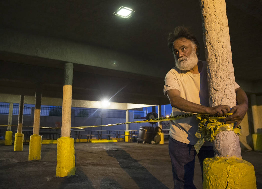 Leo Afshar, a staff member at the Southern Nevada Community Health Improvement Program, preps the sleeping area at the city of Las Vegas' homeless courtyard on Thursday, July 27, 2018, in Las Vega ...