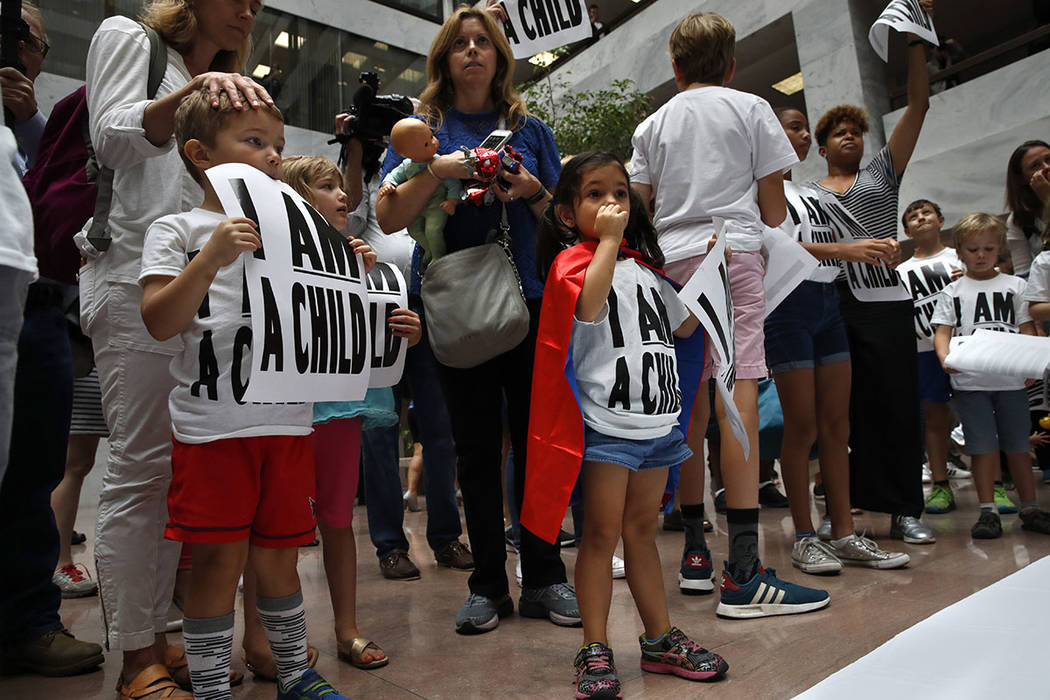 Areva Gopal, 3, of Arlington, Va., center, attends a protest of families asking for the reunification of immigrant families who were separated at the border, Thursday, July 26, 2018, on Capitol Hi ...