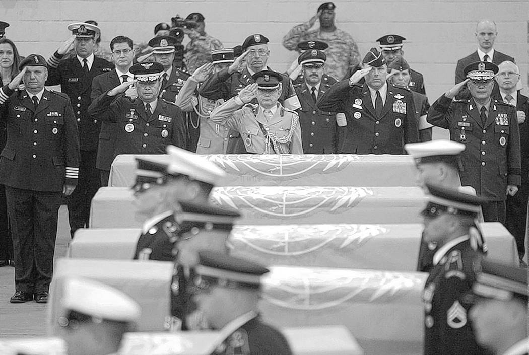 In this April 12, 2007, file photo, delegates of countries which participated in the Korean War salute the United Nations flag-covered coffins of six U.S. soldiers from the Korean War, during a te ...