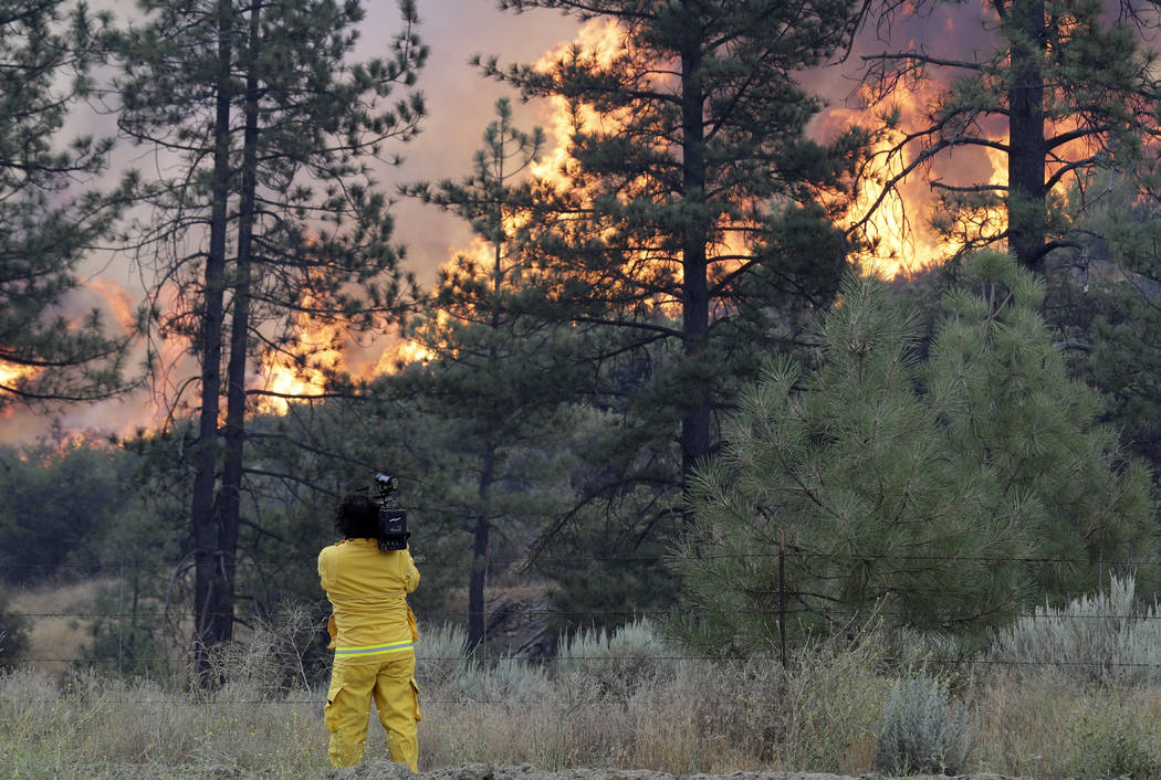 A news photographer shoots video of a wildfire along highway 74, Thursday, July 26, 2018, near Mountain Center, Calif. (AP Photo/Marcio Jose Sanchez)