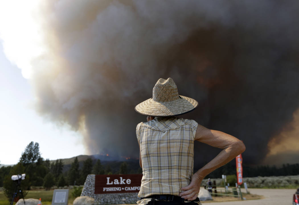 A woman watches a plume of smoke from a wildfire Thursday, July 26, 2018, in Mountain Center, Calif. A fast-moving wildfire, believed to have been sparked by arson, tore through trees, burned home ...