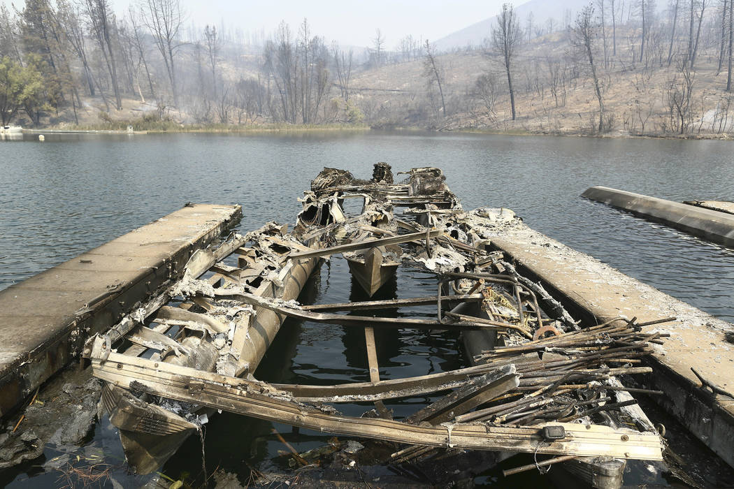 The remains of a boat burned by a wildfire is seen on a lake Thursday, July, 26, 2018, in Whiskeytown, Calif. (Hung T. Vu/The Record Searchlight via AP)