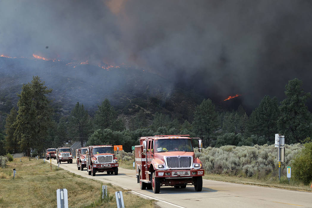 Emergency personnel travel along highway 74 as a wildfire burns a mountain, Thursday, July 26, 2018, in Mountain Center, Calif. A fast-moving wildfire, believed to have been sparked by arson, tore ...