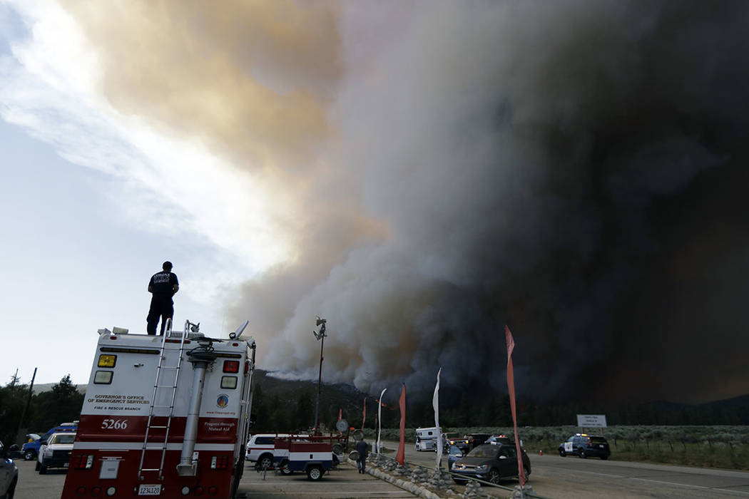 Smoke from a wildfire rises over highway 74, Thursday, July 26, 2018, in Mountain Center, Calif. A fast-moving wildfire, believed to have been sparked by arson, tore through trees, burned homes an ...