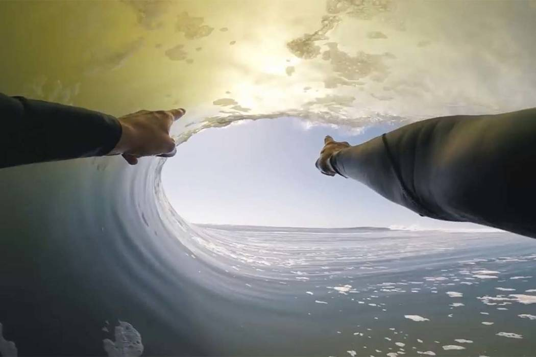In this image made from video provided by Chris Rogers, surfer Koa Smith points at a wave during his two-minute ride off the coast of Namibia on the western shore of Africa. Smith rode the wave fo ...
