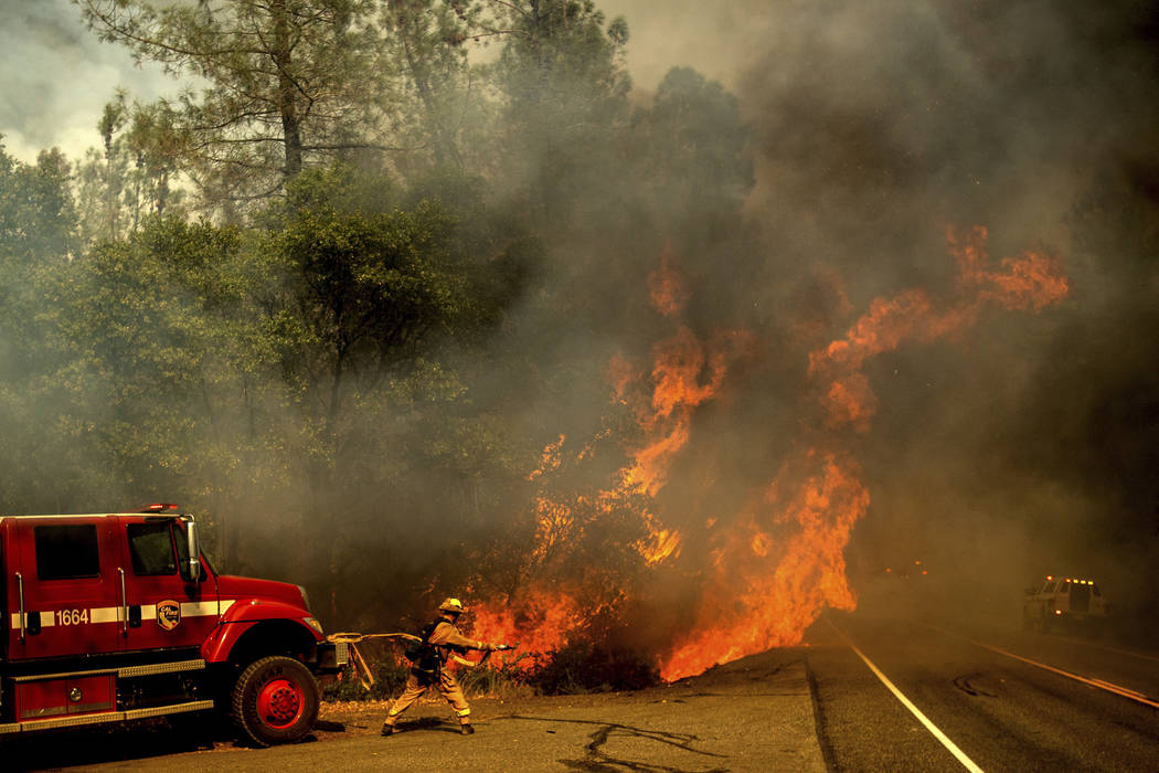 A firefighter battles the Carr Fire as it burns near Shasta, Calif., on Thursday, July 26, 2018. (AP Photo/Noah Berger)