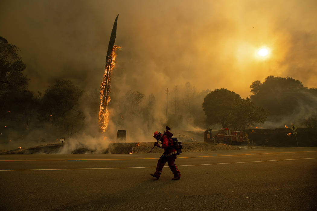 An inmate firefighter walks along Highway 299 as the Carr Fire tears through Shasta, Calif., Thursday, July 26, 2018. Fueled by high temperatures, wind and low humidity, the blaze destroyed multip ...