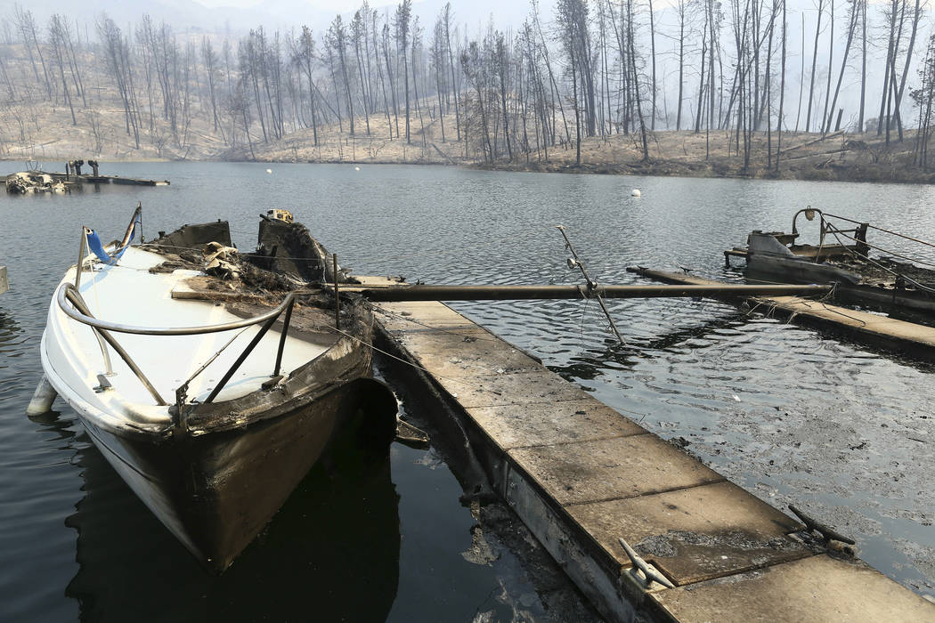 A sailboat burned by a wildfire is seen on a lake Thursday, July, 26, 2018, in Whiskeytown, Calif. California Gov. Jerry Brown has declared states of emergency in Riverside and Shasta counties as ...
