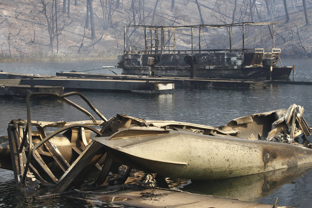 The remains of boats burned by the Carr Fire are seen on a lake Thursday, July, 26, 2018, in Whiskeytown, Calif. California Gov. Jerry Brown has declared states of emergency in Riverside and Shast ...