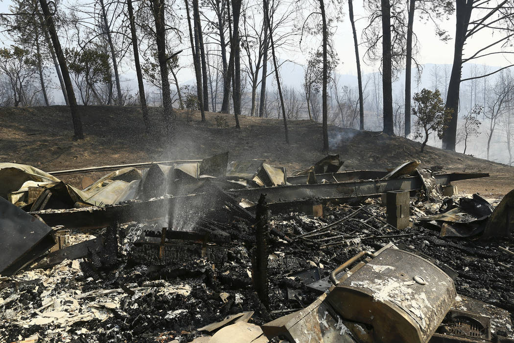 The remains of a home burned by a wildfire is seen Thursday, July, 26, 2018, in Whiskeytown, Calif. California Gov. Jerry Brown has declared states of emergency in Riverside and Shasta counties as ...