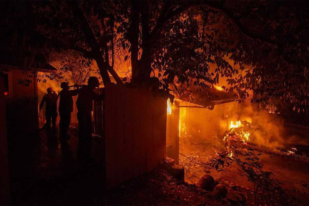 Firefighters work to battle the Carr Fire at a home in Redding, Calif., Thursday, July 26, 2018. (Daniel Kim/The Sacramento Bee via AP)