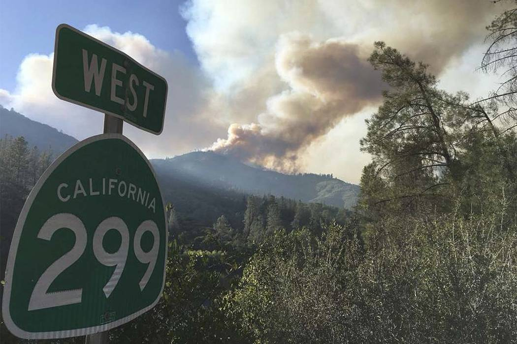 In this Wednesday, July 25, 2018 photo provided by the California Highway Patrol, the Carr Fire burns near Highway 299 and Redding, Calif. The fire is one of several across California amid a heat ...