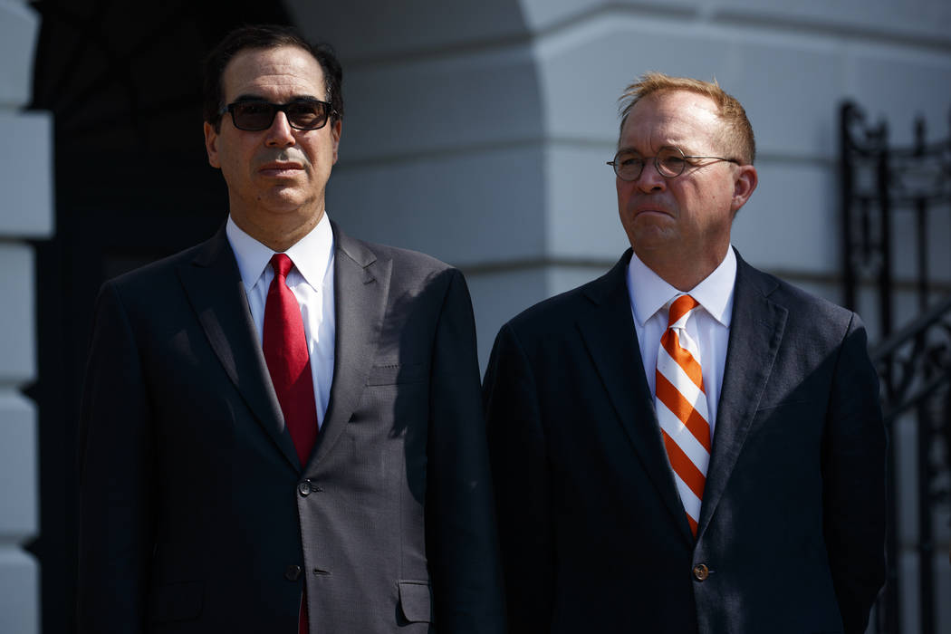 Treasury Secretary Steve Mnuchin, left, and Director of the Office of Management and Budget Mick Mulvaney listen as President Donald Trump delivers remarks about the economy on the South Lawn of t ...