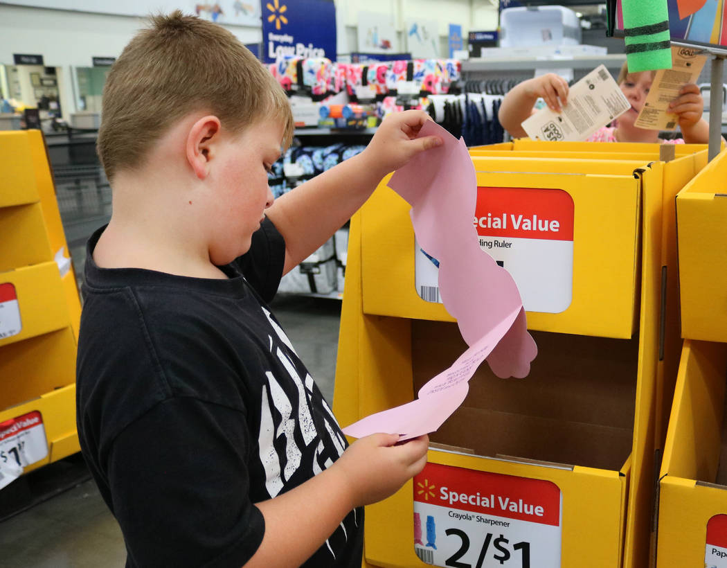 Brady LeBowsky, 6, examines a notepad at Walmart in Las Vegas while his sister Chloe, 8, looks at pencils on Thursday, July 26, 2018. The two went back-to-school shopping with their mother, Laura ...