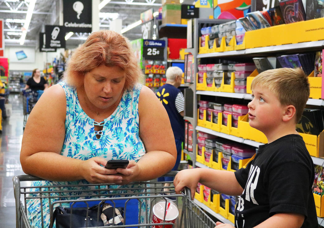 Laura LeBowsky, left, refers to a shopping list on her phone at Walmart her son Brady, 6, stands by patiently in Las Vegas, Thursday, July 26, 2018. The list provided by her children's school has ...