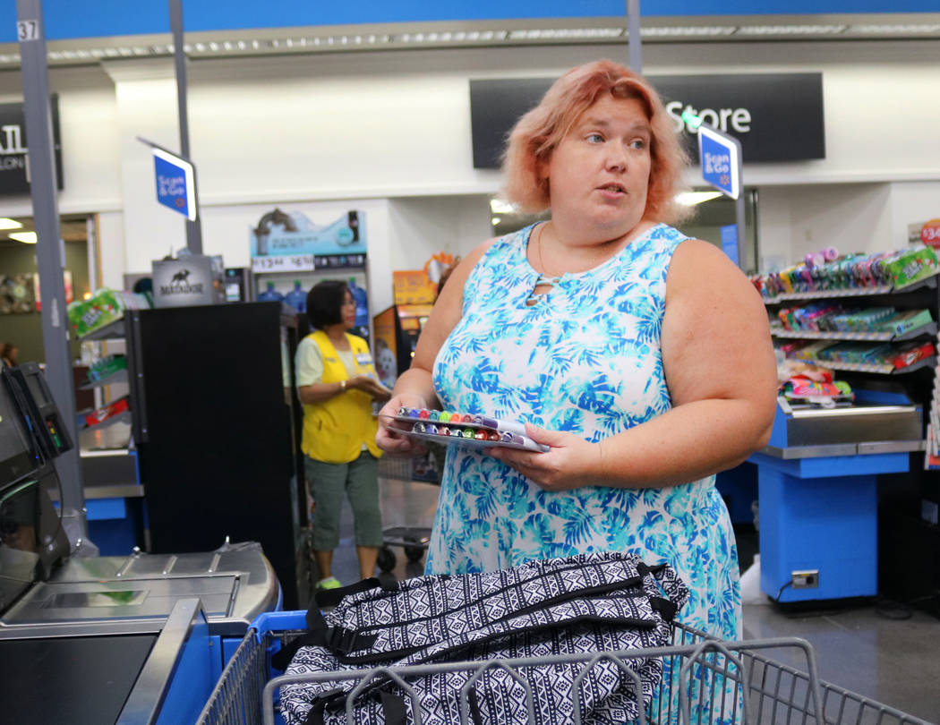Laura LeBowsky, uses the self checkout after going back to-school-shopping at Walmart in Las Vegas, Thursday, July 26, 2018. The list provided by her children's school has all of the items her two ...