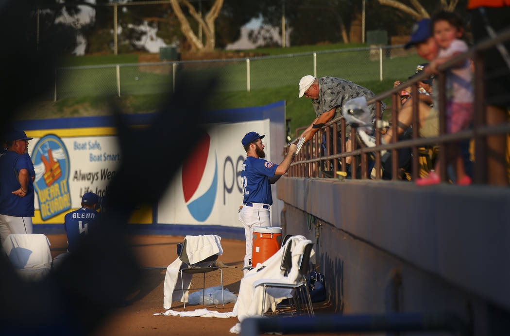 Las Vegas 51s pitcher Bobby Wahl (32) signs an item for Bill Haws before the start of a baseball game against the Nashville Sounds at Cashman Field in Las Vegas on Thursday, July 26, 2018. Chase S ...
