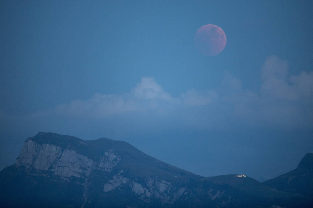The moon turns red during a total lunar eclipse, as seen from Lucerne, Switzerland, Friday, July 27, 2018. Skywatchers around much of the world are looking forward to a complete lunar eclipse that ...