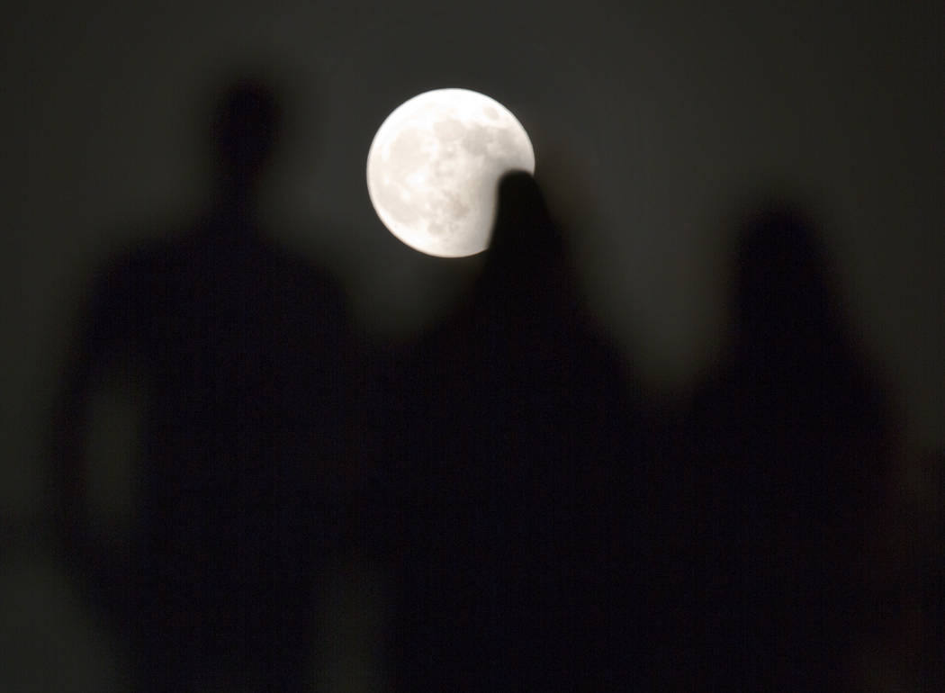 People watch the lunar eclipse at the Children's Civilization and Creativity Center in Cairo, Egypt, Friday, July 27, 2018. Skywatchers around much of the world are looking forward to a complete l ...