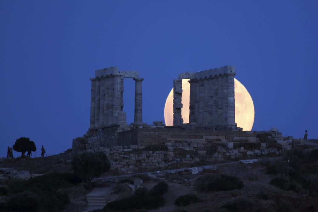 A full moon rises behind the ancient temple of Poseidon in cape Sounio, about 65 kilometers (40miles) south of Athens, Friday, July 27, 2018. The complete lunar eclipse Friday when the sun, Earth ...