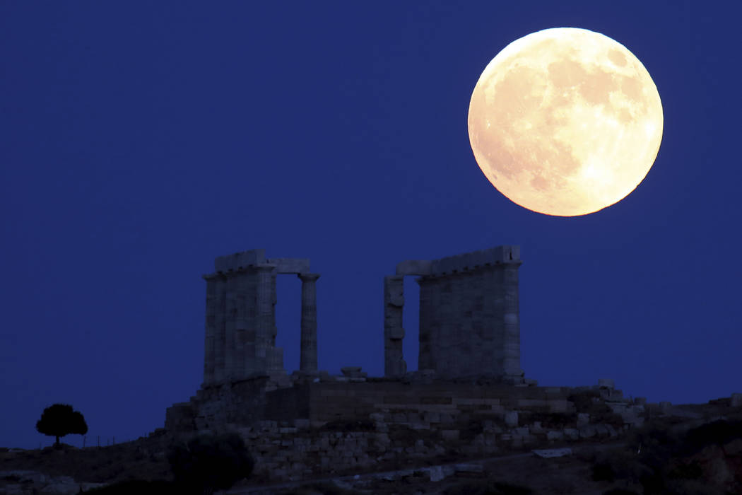 Full moon rises over the ancient temple of Poseidon in cape Sounio, about 65 kilometers (40miles) south of Athens, Friday, July 27, 2018. The complete lunar eclipse Friday when the sun, Earth and ...