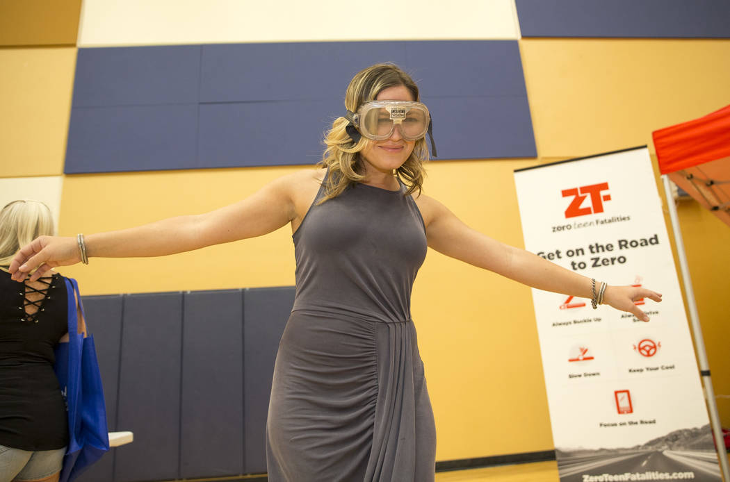 Las Vegas resident Stephanie Bullock attempts to walk a straight line while demoing the Fatal Vision goggles, customized goggles used to simulate alcohol impairment, at the Nevada Highway Patrol b ...