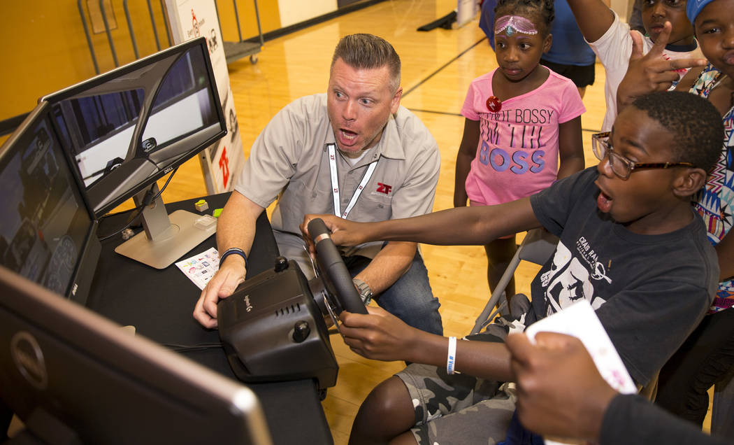 Jason Ealy, left, of Zero Teen Fatalities, and Zion Robinson, 8, react as Robinson crashes in a driving simulator demonstration during the Citywide Traffic Safety Block Party hosted by the Las Ve ...