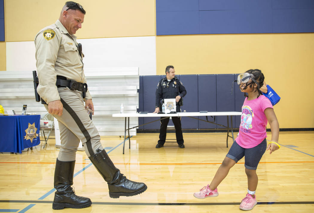 Metropolitan Police Department traffic bureau officer Michael Lemley administers a mock field sobriety test to five-year-old Jordan Rowe during the Citywide Traffic Safety Block Party hosted by th ...